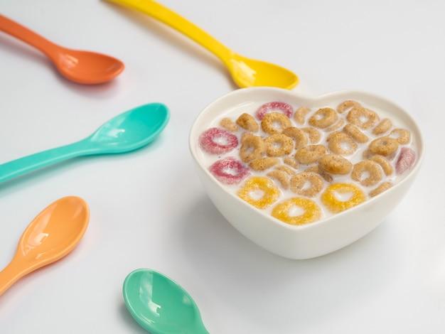 Tazón con cereales y cucharas a su lado Foto gratis
