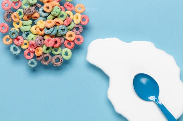Tazón de cereales y salpicaduras de leche con cuchara azul Foto gratis