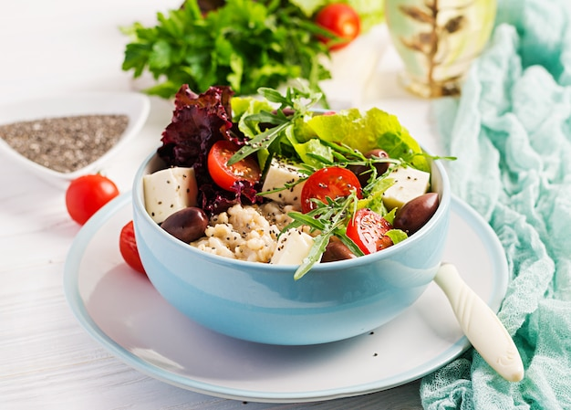 Tazón de desayuno con avena, tomate, queso, lechuga y aceitunas. comida sana. tazón de buda vegetariano Foto Premium