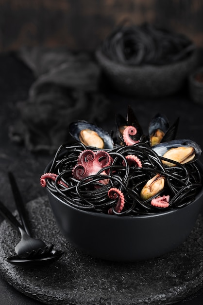Tazón con espagueti negro y mejillones Foto gratis