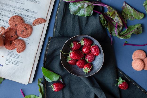 Tazón de fresas y galletas, hojas de espinaca, un libro sobre una estera negra. Foto gratis
