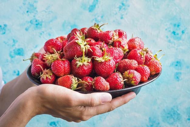 Tazón con fresas maduras en sus manos. Foto Premium