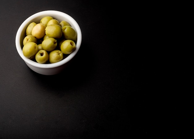 Tazón de fuente de aceituna fresca verde sobre fondo negro Foto gratis