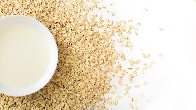 Tazón de leche saludable sobre las copos de avena seca sobre el fondo blanco Foto gratis