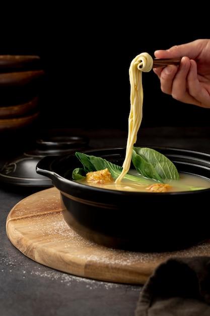Tazón negro con sopa de fideos en un plato de madera Foto gratis