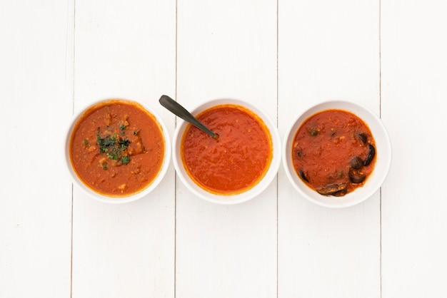 Tazón de salsa roja vívida dispuesta en fila en la mesa blanca de madera Foto gratis