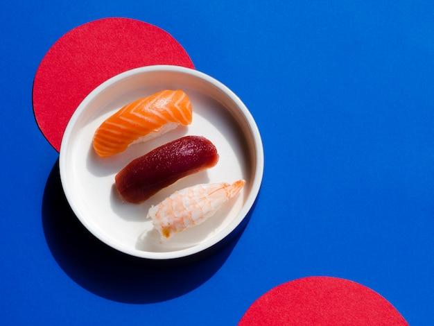 Tazón de sushi sobre un fondo rojo y azul Foto gratis