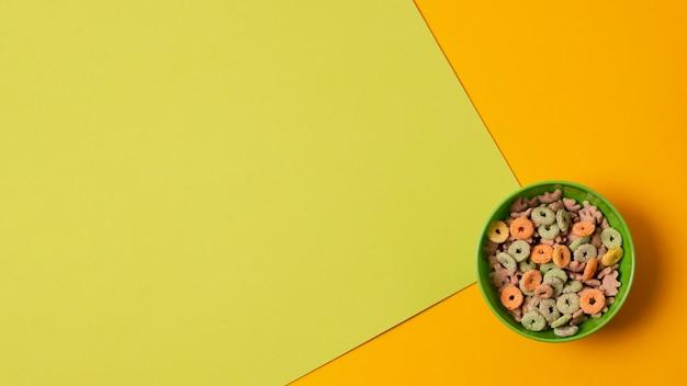 Tazón verde vista superior con cereales coloridos Foto gratis