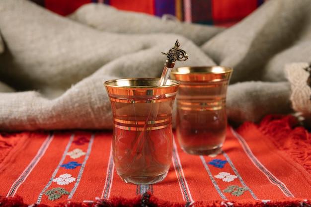Té árabe en vasos en mesa roja Foto gratis
