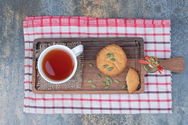 Té aromático en taza blanca con galletas y semillas de calabaza en la mesa de mármol Foto gratis