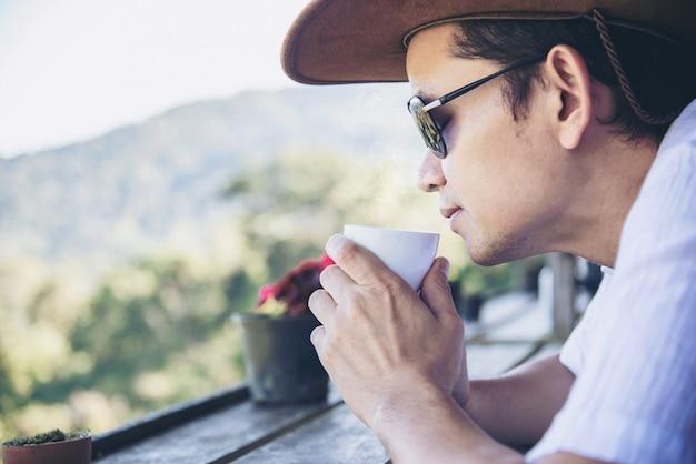 Té caliente de la bebida del hombre con el fondo de la colina verde - la gente se relaja en concepto de la naturaleza Foto gratis