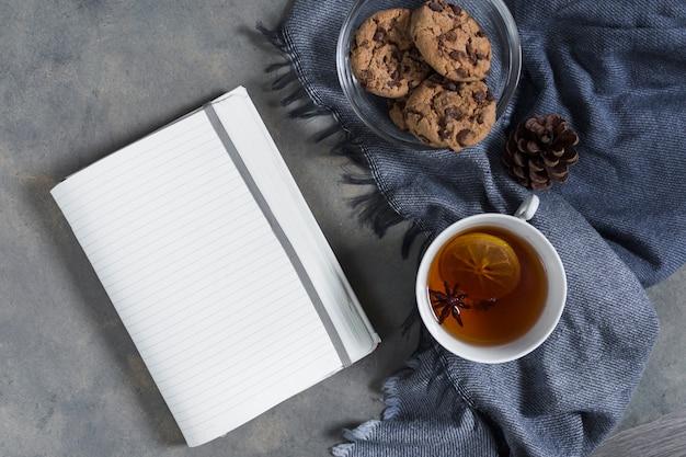 Té con galletas en cuadros azul con libreta Foto gratis