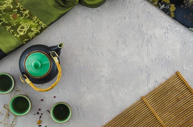 Té de hierbas oriental con textiles asiáticos y mantel sobre fondo texturizado Foto gratis