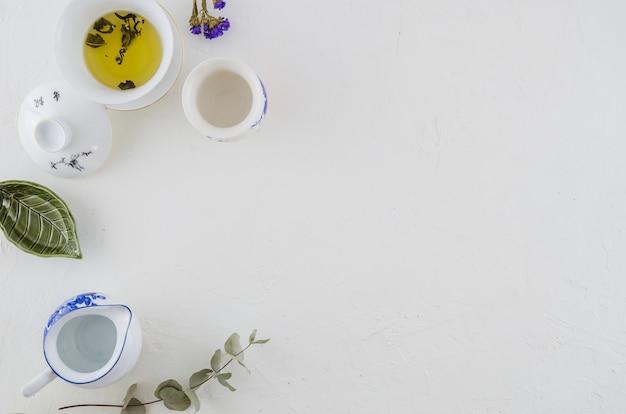 Té de hierbas en un tazón de cerámica china; jarra y una taza aislada sobre fondo blanco Foto gratis