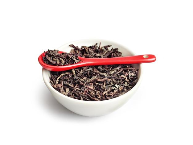Té de hojas secas en un recipiente con cuchara de cerámica roja aislada en blanco Foto Premium