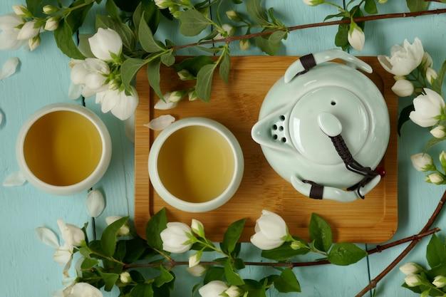 Té de jazmín. té orgánico puro de flores. té de jazmín en tazas redondas de color verde claro, tetera y ramas de jazmín. Foto Premium