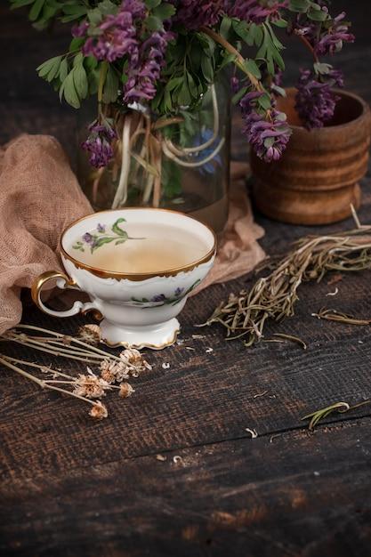 Té con limón y bouquet de prímulas sobre la mesa Foto gratis