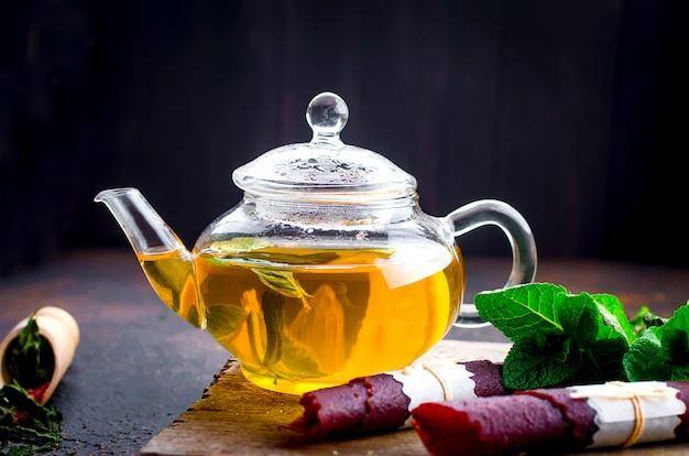 Té de menta caliente en una tetera y rollo de cuero de frutas secas Foto Premium