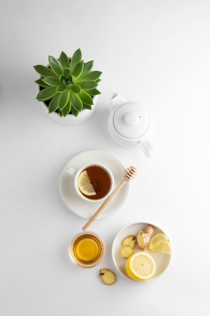 Té negro con limón y miel sobre un fondo blanco. taza de té caliente aislado, vista superior plana. endecha plana. bebida de otoño, otoño o invierno. copyspace Foto Premium