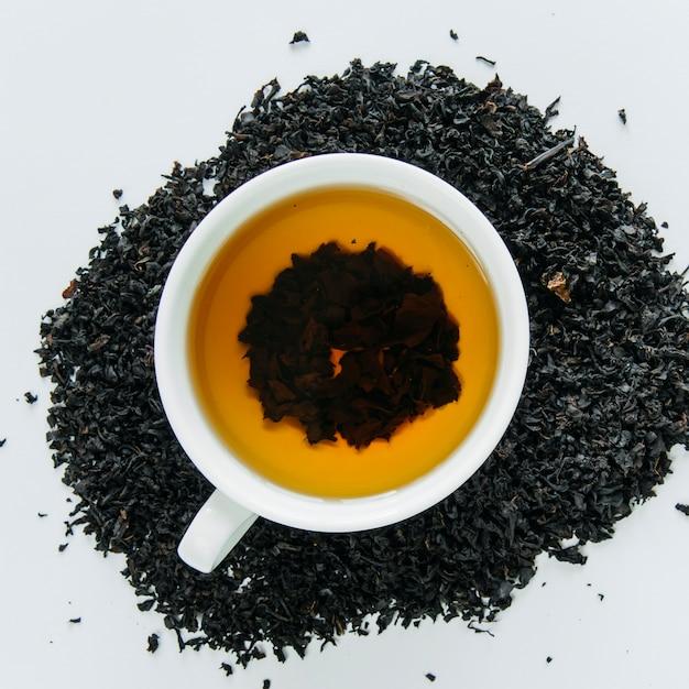 Té negro en una taza y hojas secas sobre fondo blanco. Foto gratis