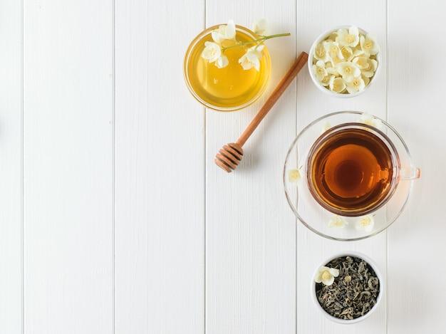 Té recién preparado con flores de jazmín y miel sobre una mesa de madera blanca Foto Premium