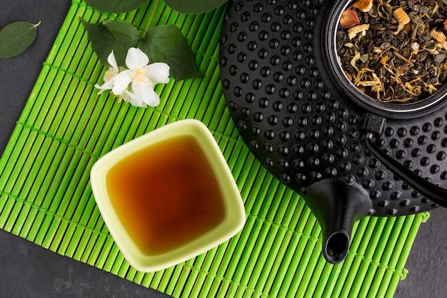 Té saludable en un tazón de cerámica con hojas secas en mantelito verde Foto gratis
