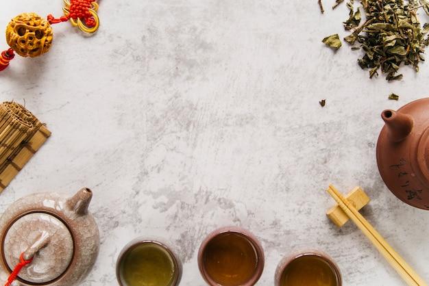 Té verde caliente en dos tazas de cerámica de arcilla china tradicional y una tetera con borla Foto gratis
