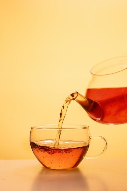 Té se vierte en una taza de té de vidrio Foto Premium