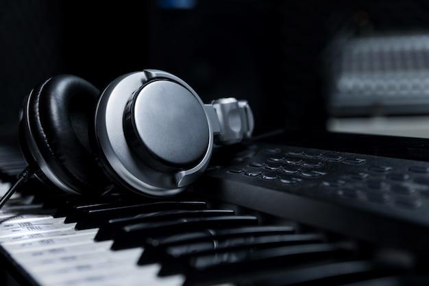 Teclado de piano con auriculares para música, auriculares con teclado de piano, primer plano, auriculares con fondo de piano eléctrico por el fondo de instrumentos musicales. Foto Premium