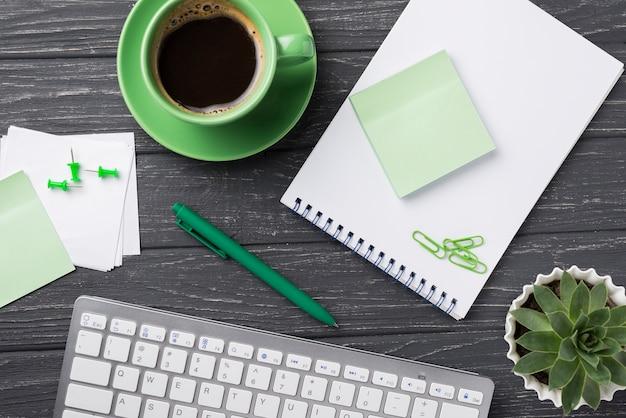 Teclado con planta suculenta y notas adhesivas sobre escritorio de madera Foto gratis