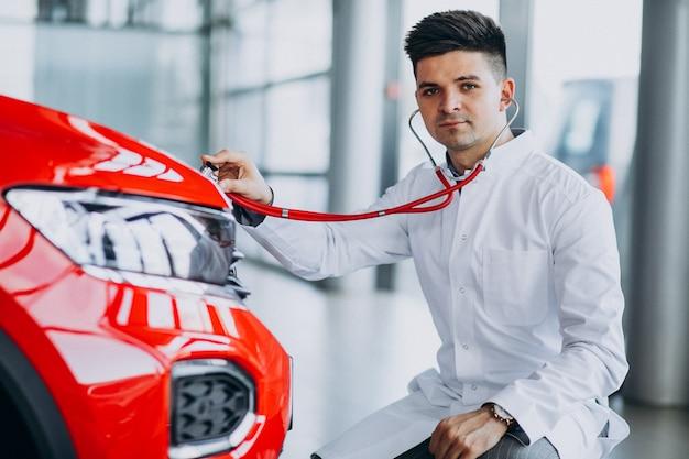 Técnico de automóviles con estetoscopio en una sala de exposición de automóviles Foto gratis