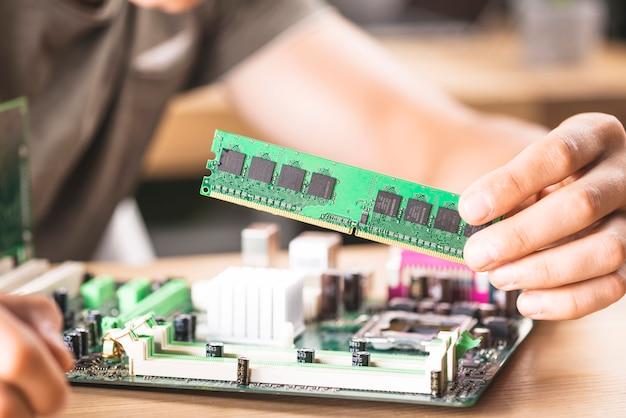 Técnico informático masculino que instala la memoria ram en la placa base Foto gratis