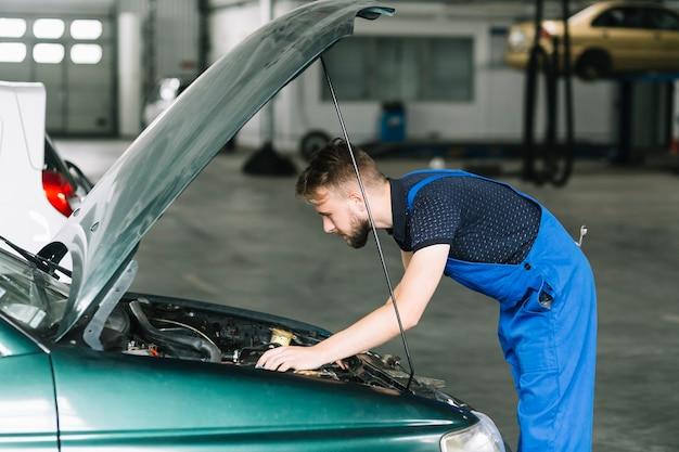 Técnico que repara el motor del coche en el garaje Foto gratis