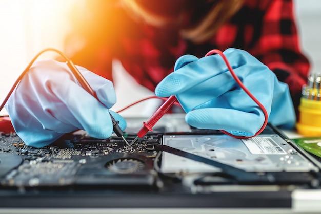 Técnico que usa un multímetro para la medición de voltaje, soporte para computadora portátil. Foto Premium