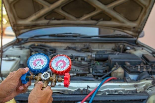 Técnico que utiliza equipos de medición para el llenado de aire acondicionado del automóvil. conceptos de servicio de reparación de automóviles y seguros de automóviles. Foto Premium