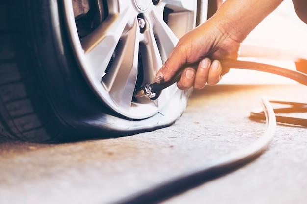 El técnico está reparando el neumático desinflado. Foto gratis