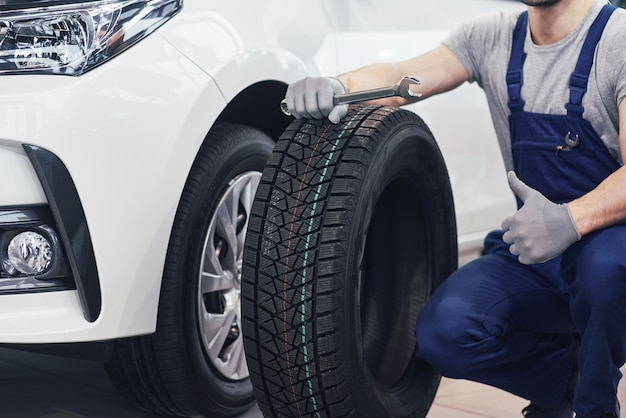 Técnico con ropa de trabajo azul, sosteniendo una llave y un neumático mientras muestra el pulgar hacia arriba Foto gratis