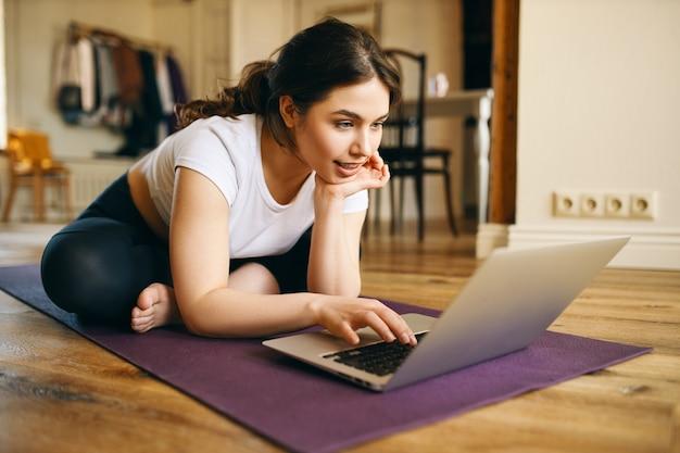 Tecnología, comunicación, aprendizaje a distancia y distanciamiento social. linda chica de talla grande con conexión inalámbrica a internet de alta velocidad en una computadora portátil, viendo el curso de instructor de yoga en línea, sentado en la alfombra Foto gratis
