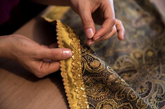Tejer cinta dorada a la alfombra. Foto gratis