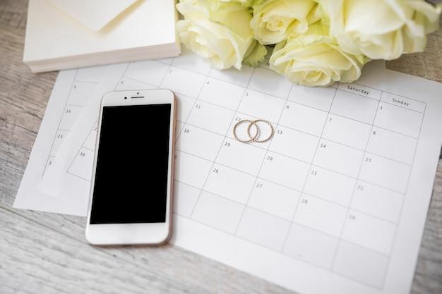 68fc6f78b450 Teléfono inteligente  anillos de boda  sobre y rosas en el calendario sobre  el tablón de madera.