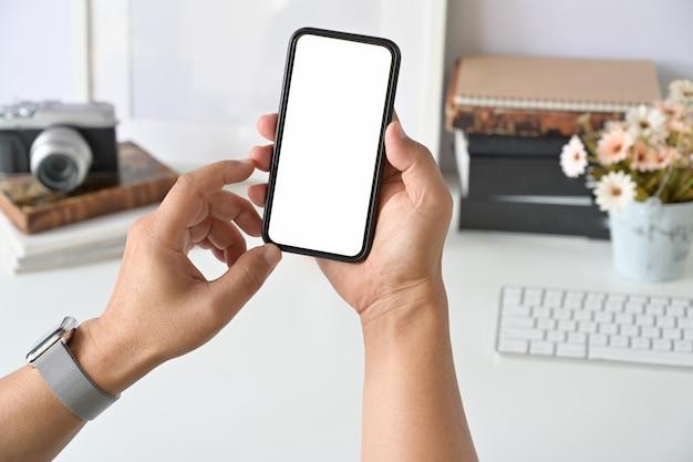 Teléfono inteligente móvil en la mano del hombre en el trabajo de escritorio. Foto Premium