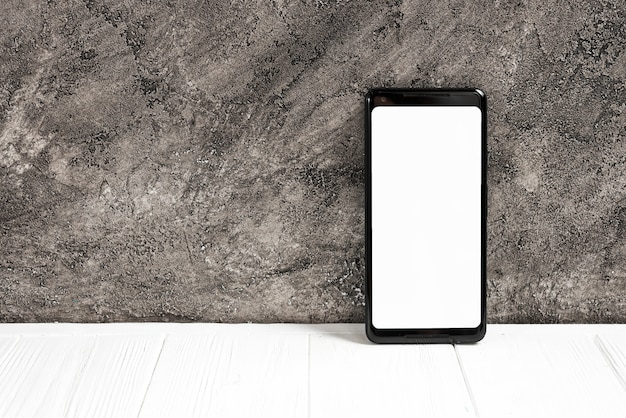 Teléfono inteligente con pantalla blanca en mesa blanca contra muro de hormigón Foto gratis