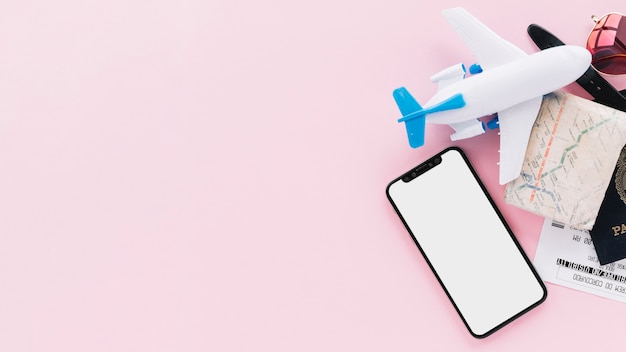 Teléfono inteligente con pantalla en blanco con pasaporte de viaje; mapa; entradas; avión de juguete y gafas de sol sobre fondo rosa Foto gratis