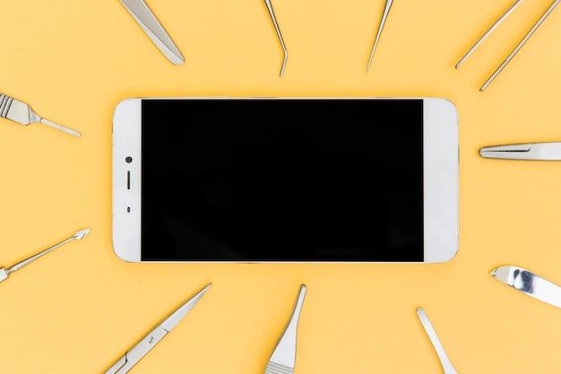 Teléfono inteligente rodeado de equipos médicos quirúrgicos sobre fondo amarillo Foto gratis