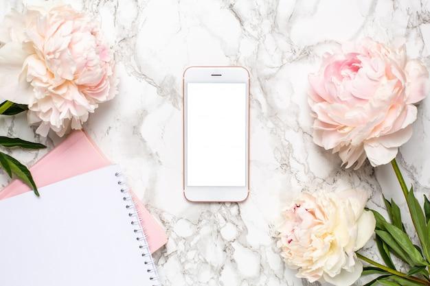 Teléfono móvil con un cuaderno blanco y rosa y flores piony sobre un fondo de mármol Foto Premium