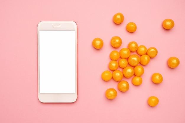 Teléfono móvil y dulces dulces amarillos en una tecnología rosa Foto Premium