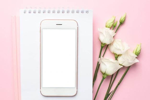 Teléfono móvil, flor blanca y cuaderno en rosa Foto Premium