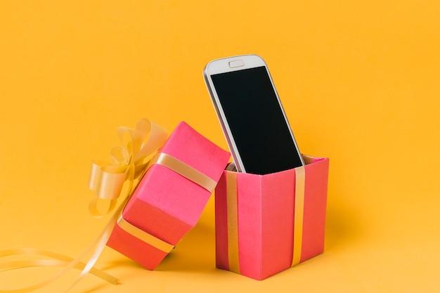Teléfono móvil con pantalla en blanco en caja de regalo rosa. Foto gratis