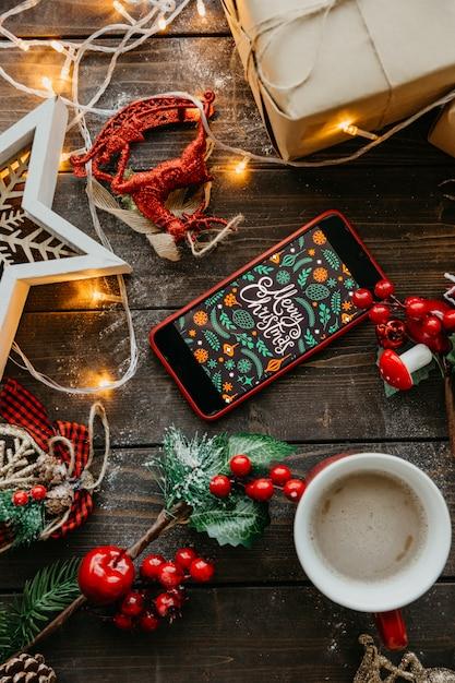 Teléfono con pantalla navideña y café con leche sobre la mesa Foto gratis