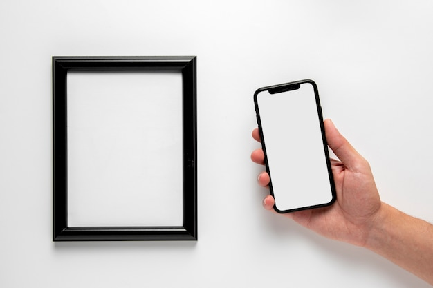 Teléfono plano junto a la maqueta del marco Foto gratis
